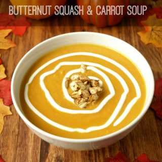 a bowl of butternut squash carrot soup ready to serve in a white bowl on a wooden table with fall accents