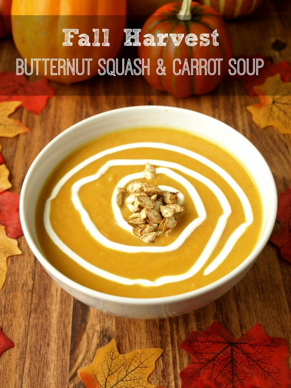 A bowl of Butternut squash carrot soup on a wooden table with fall pumpkin and leaf accents
