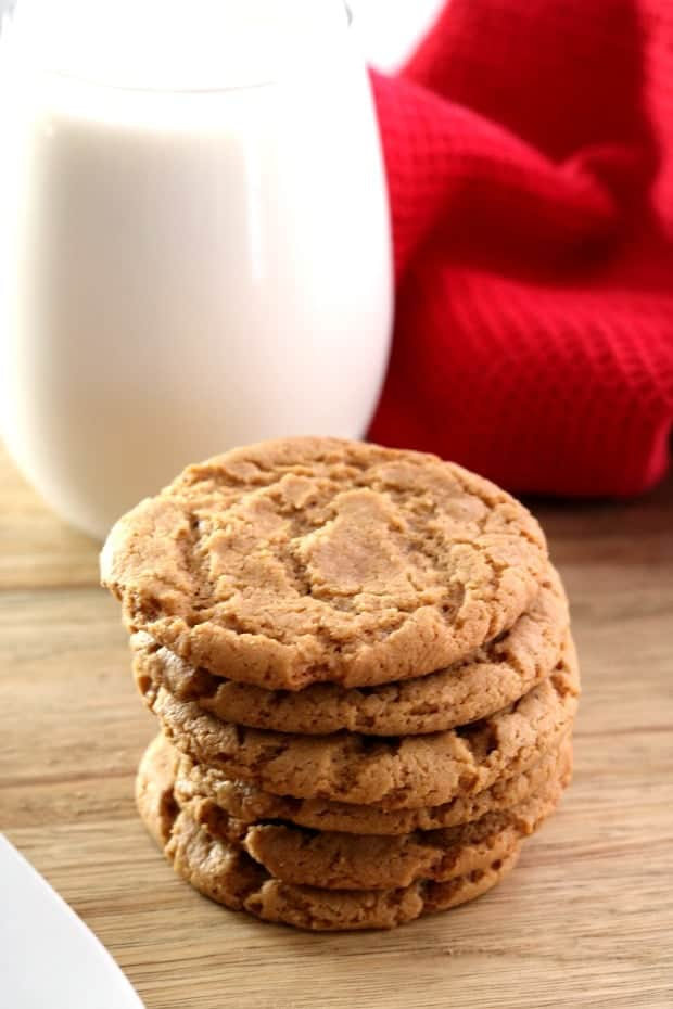 A stack of gingersnap cookies with a glass of milk.
