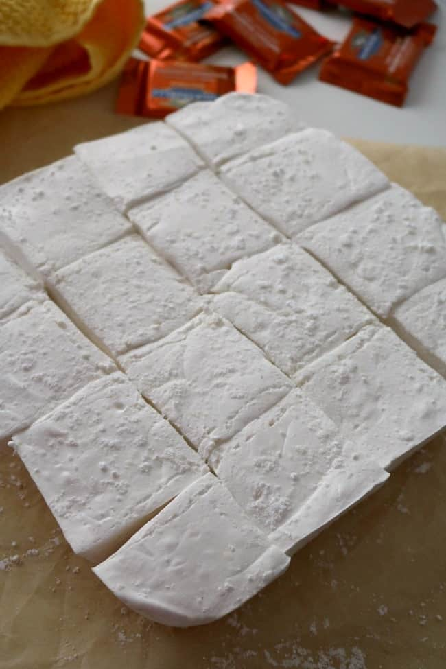 Freshly made marshmallows cut into squares with individually-wrapped square dark chocolates in the background.