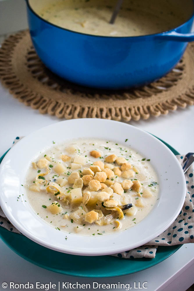 A bowl of creamy clam chowder with crackers on top.