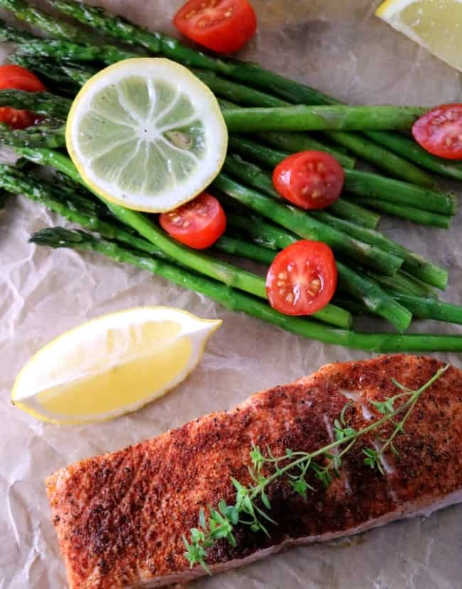 An image of cajun salmon on brown parchment with roasted asparagus, quartered grape tomatoes, and a lemon wedge.