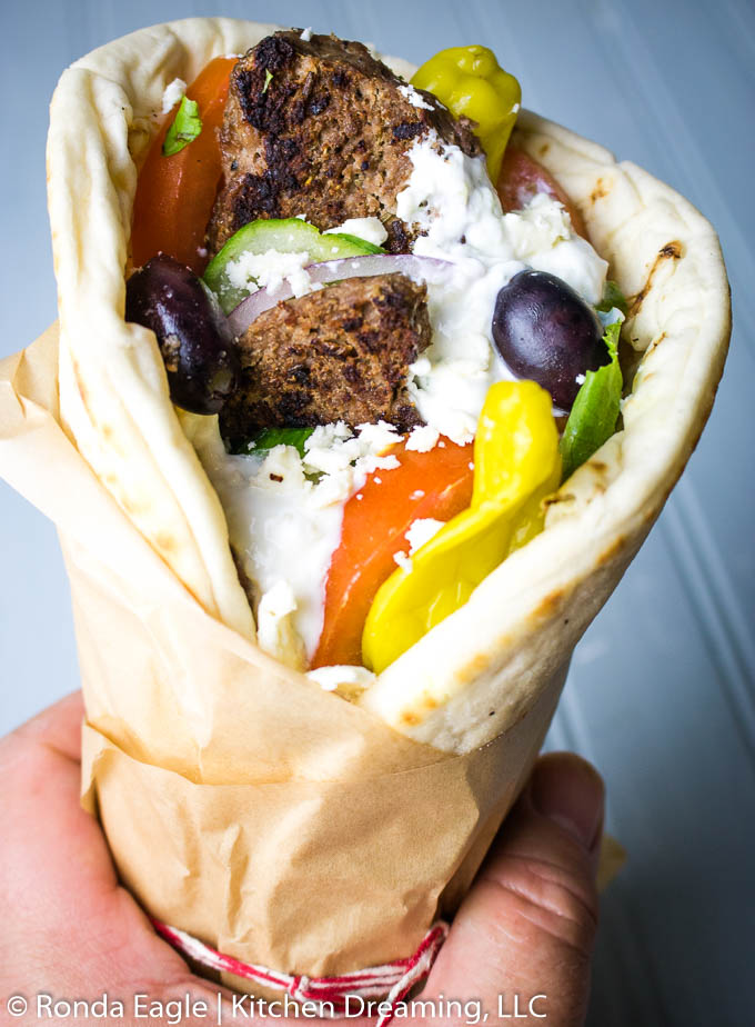 A hand holding a gyro wrap filled with meat, lettuce, tomatoes, cucumbers, olives, hot peppers, tzatziki sauce, and crumbled feta cheese.