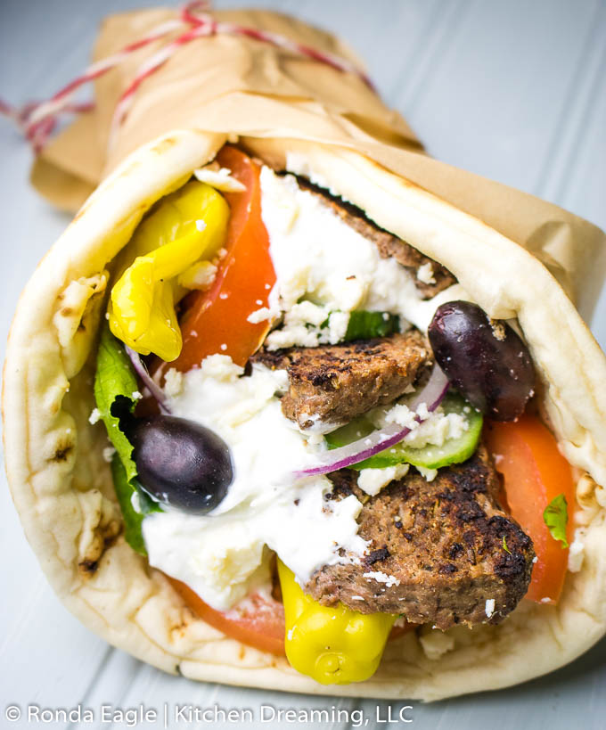 Another long view of a gyro wrapped in a fresh pita layered with shredded lettuce, tomatoes, red onion, cucumbers, kalamata olives, pepperoncini peppers, tzatziki sauce, and crumbled feta cheese.