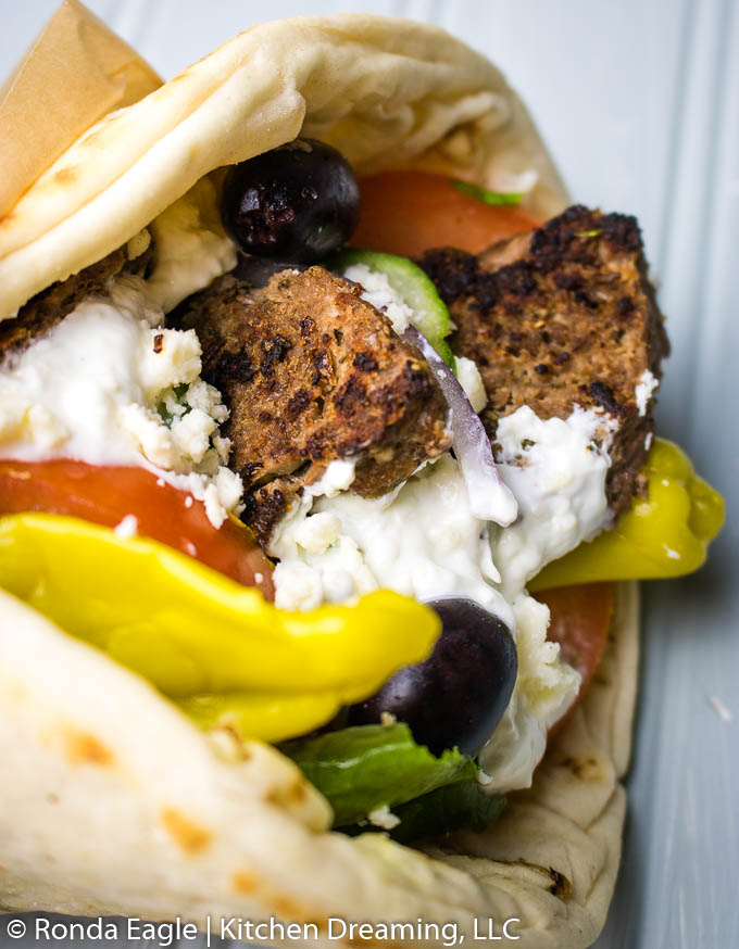 homemade gyro meat wrapped in a fresh pita layered with shredded lettuce, tomatoes, red onion, cucumbers, Kalamata olives, pepperoncini peppers, tzatziki sauce, and crumbled feta cheese.