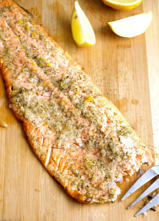 a side of baked steelhead trout on a wooden cutting board with slices of fresh lemon.