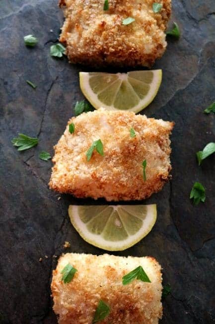 3 pieces of Panko Crusted Baked cod fish on a black slate tile. Each piece of cod fish has a lemon slice between it.