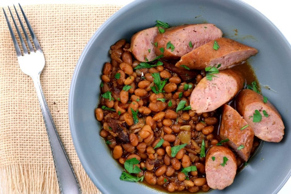 An overhead photo of a bowl of Baked Beans with sausages.