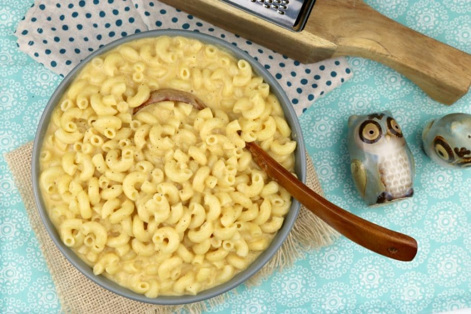 An overhead landscape photo of a bowl of homemade mac and cheese. A wooden spoon sticks out of the serving bowl.