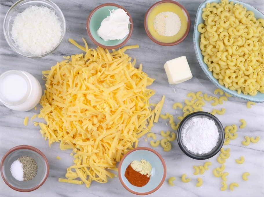 A lansdscape image of the ingredients for homemade Mac and Cheese Recipe. Macaroni, flour, butter, herbs, spices, milk, 3-cheese blend.