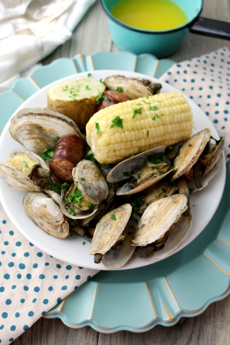 A bowl filled with steamer clams, corn, and sausages. A small pot of drawn butter site on the table behind the bowl. The white bowl is sitting on a blue polka dotted napkin and a light blue charger plate. A white towel is in the background.