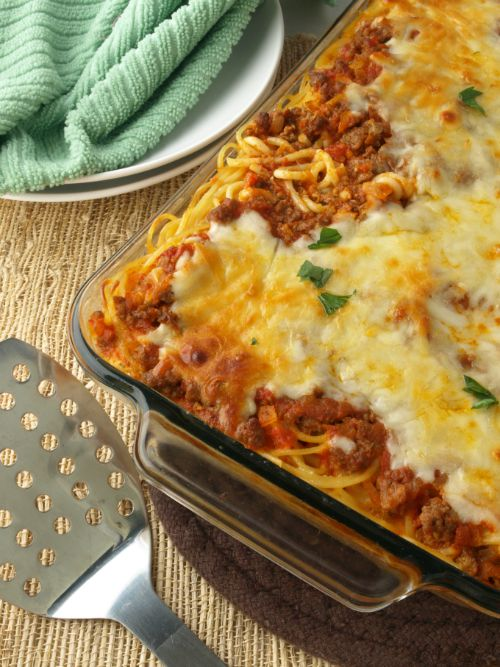 In image of a baked spaghetti casserole in a glass baking dish and a spatula.