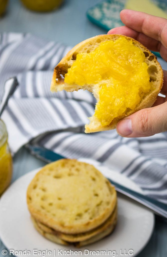 An image showing a close-up photo of pineapple jam spread on a toasted and buttered English muffin. A bite has been taken out of the English muffin. A plate of toasted muffins is seen below in the background along with a partial view of a jar of pineapple jam.