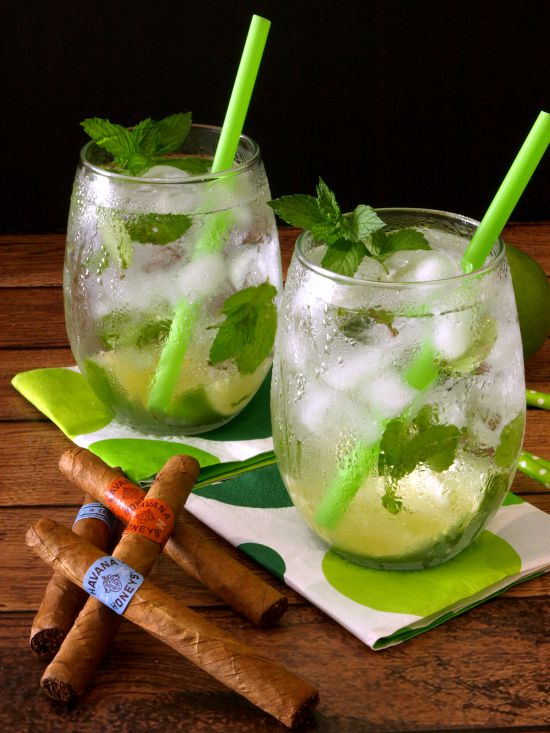 Two glasses of Cuban Mojitos with fresh mint and lime with green straws