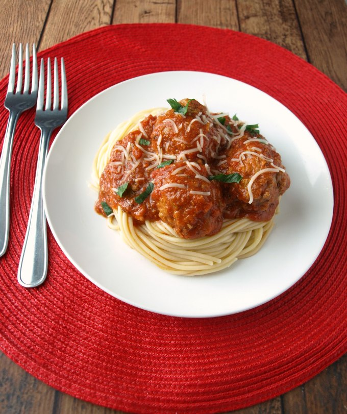 A 3/4 angle photo of meatballs, spaghetti, and sauce on a plate.