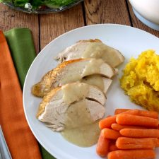 A plate of turkey breast meast with gravy, carrots and butternut squash