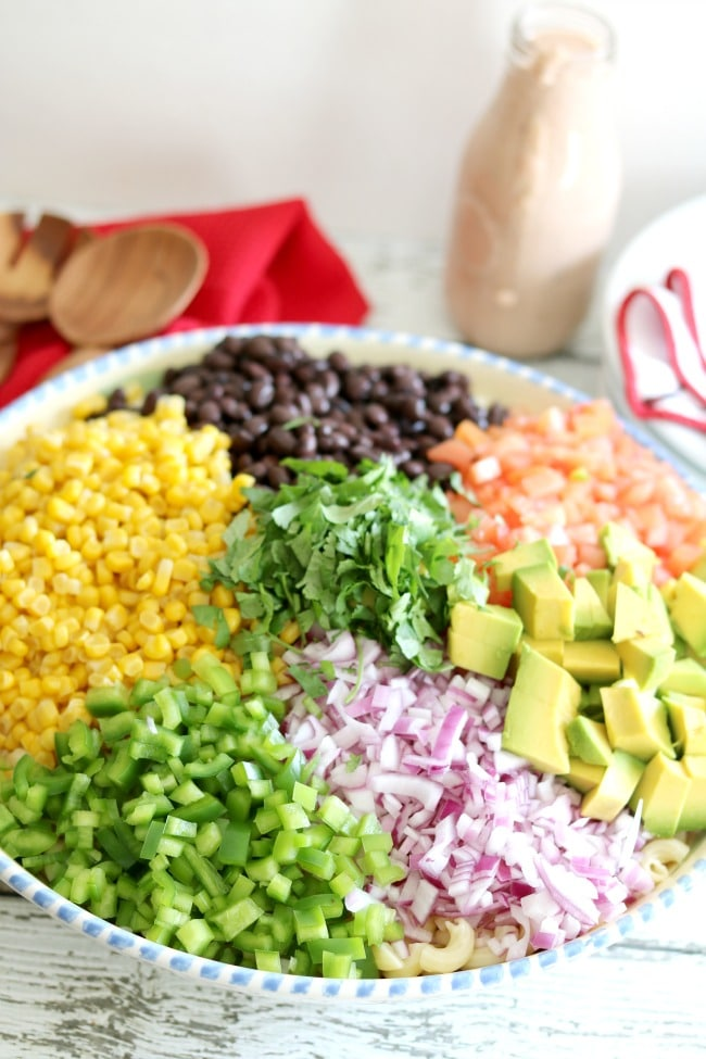 The chopped ingredients for Mexican Macaroni salad layers in a bowl.