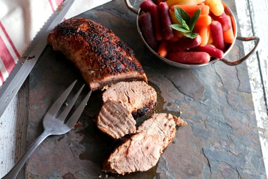 Overhead shot of a Pork Tenderloin on a dark slate tile with rainbow carrots and a fork and carving knife.
