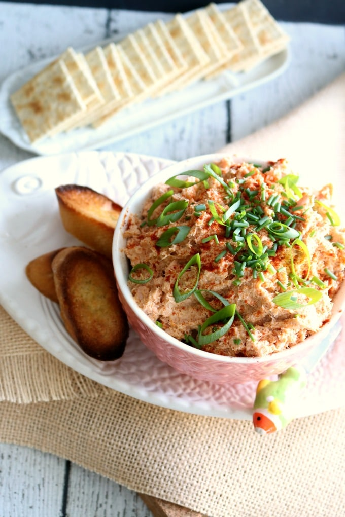 Salmon Rillettes in a bowl on a platter with crackers