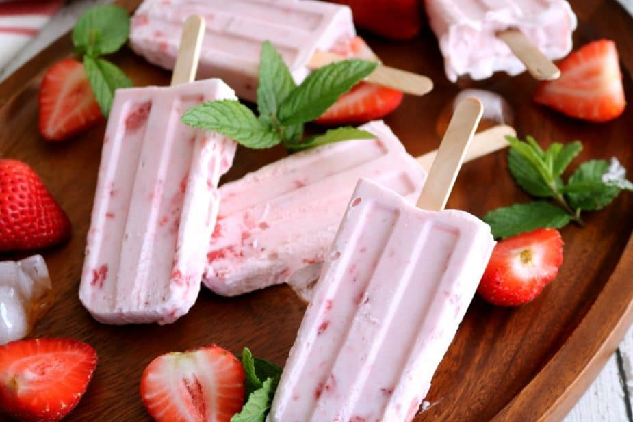 A wooden tray of strawberry Cream Popsicles with sliced strawberries and ice cubes.