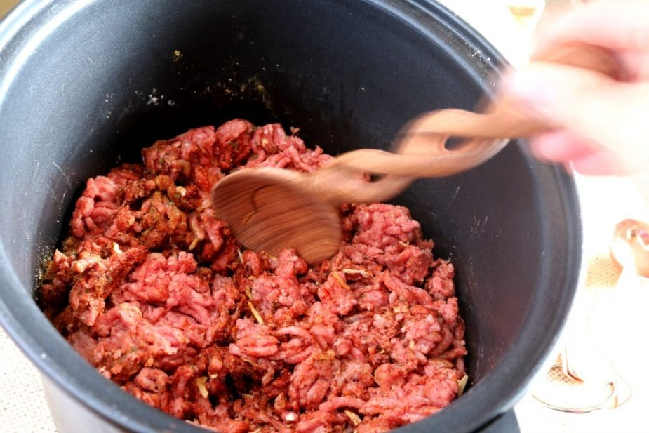 Ground beef in the slow cooker insert ready to be mixed with the taco seasoning and cooked.