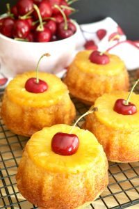 Pineapple upside-down cake is simply a basic yellow cake which is inverted after baking to reveal a glistening sheen of caramelized butter and brown sugar coating golden pineapple and maraschino cherries.