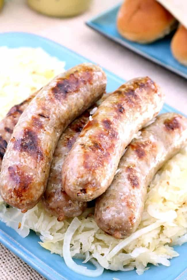 A plate of grilled brats on top of braised onions and sauerkraut.