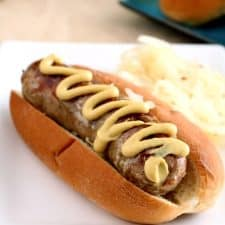 A grilled bratwurst in a soft bun topped with a zig-zag of spicy brown mustard.