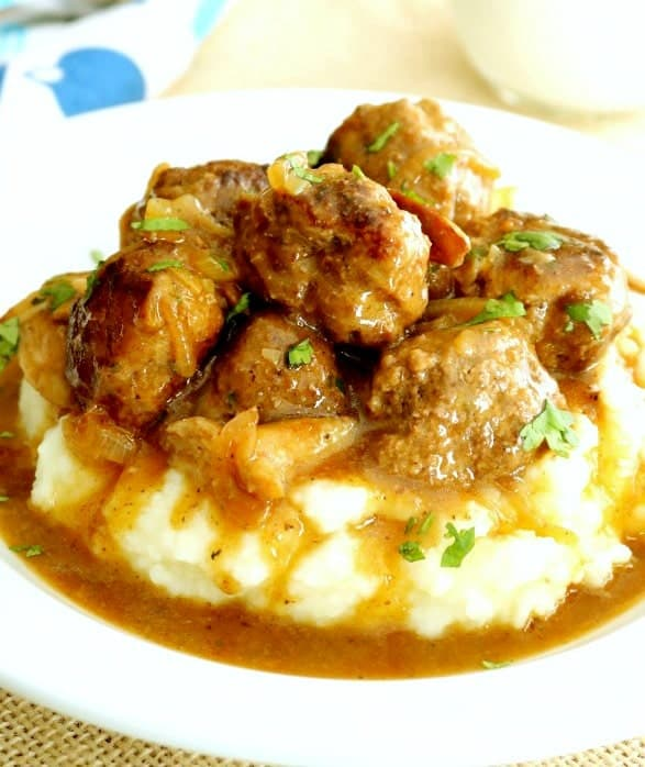 A close-up of a white plate containing salisbury steak meatballs smothered in homemade brown gravy on a bed of mashed potatoes.