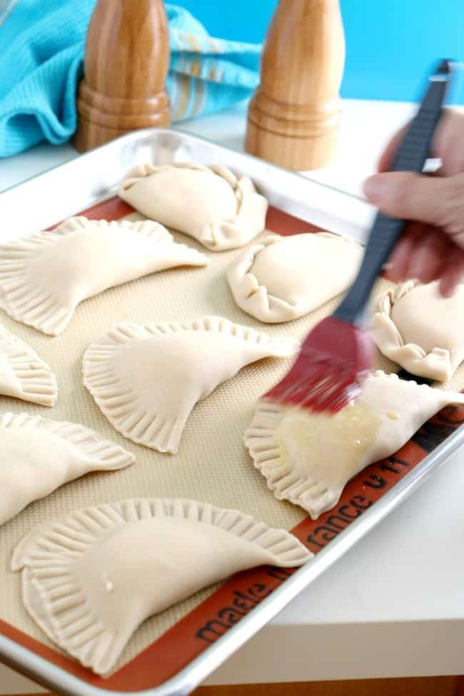 An image of stuffed empanadas being prepared with egg wash for the oven