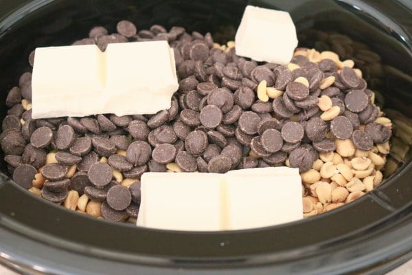 A slow cooker layered with ingredients for chocolate peanut clusters; peanuts, bittersweet dark chocolate, and almond bark.