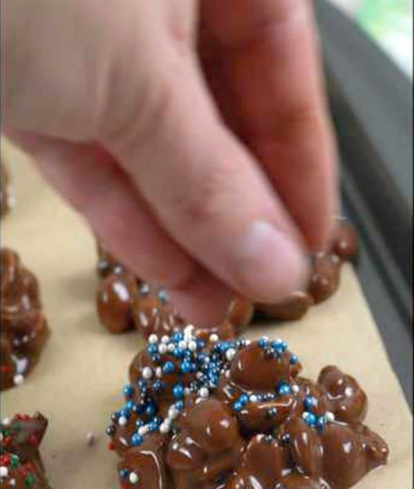 Festive sprinkles being added to a chocolate peanut cluster after it has been portioned but before the chocolate has set.