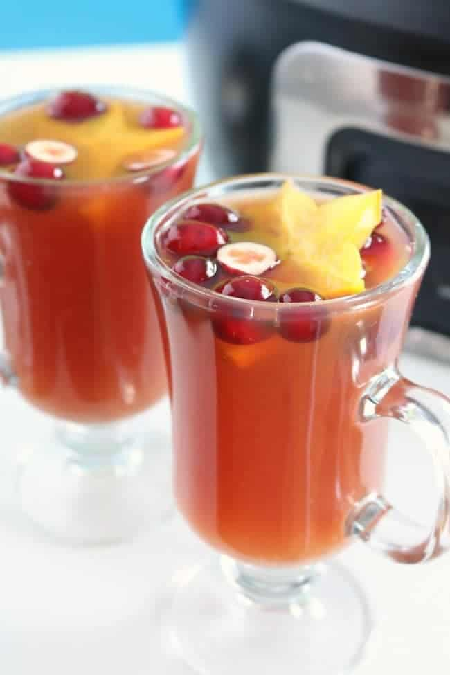 A close up photo of two clear glass mugs filled witharm holiday punch