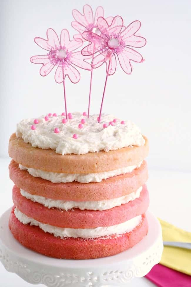 A pink ombre cake on a stand