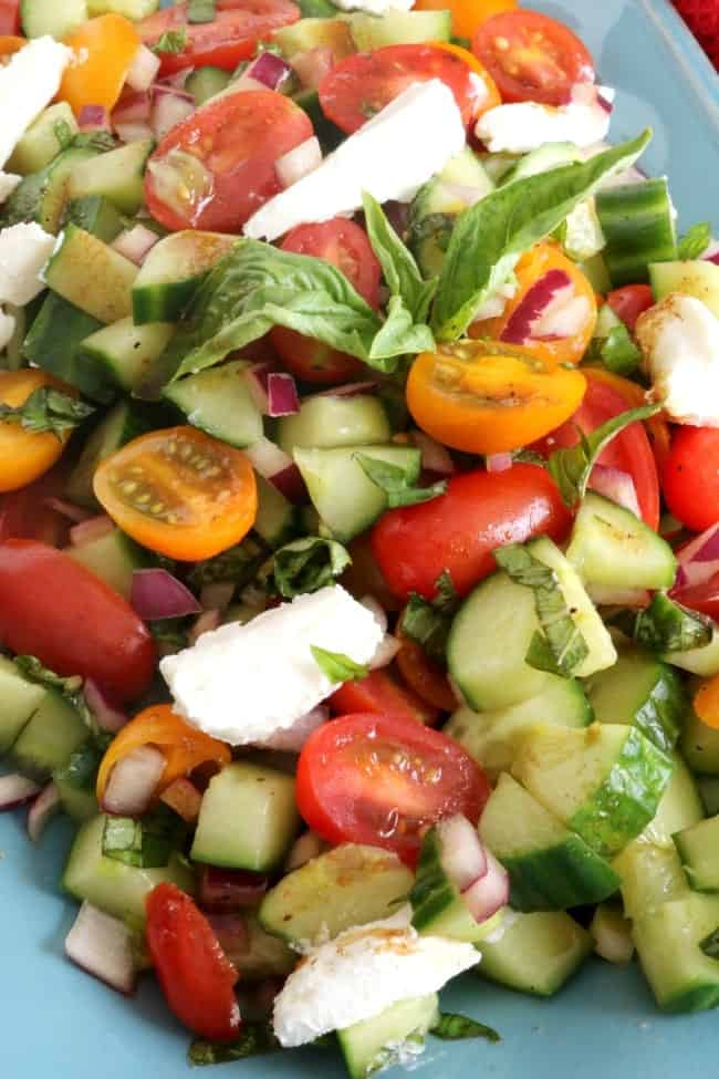 Tomato basil cucumber salad uses just a few simple ingredients which also makes it quick and easy to prepare. Beautiful red and orange (or yellow) cherry tomatoes, cucumbers, fresh basil, and red onions combine with tangy goat cheese to create the perfect balance.