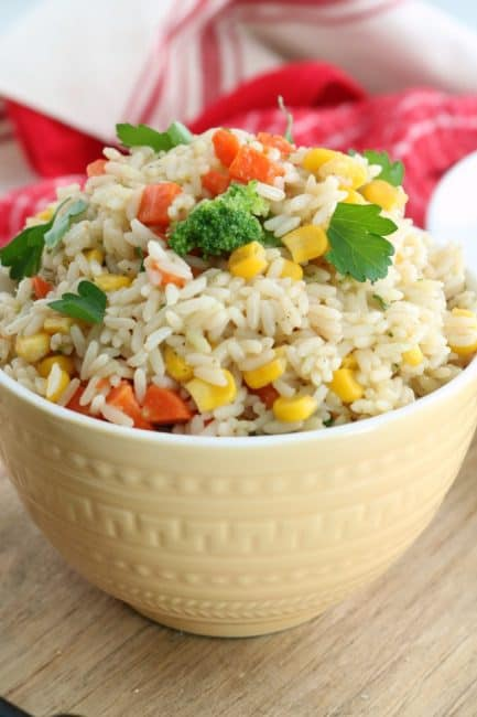 A bowl of garbed vegetable rice ready for serving. The rice is made with long grasin white rice and your favorite variety of vegetables. In this case carrots, corn, and broccoli can be seen. The rice is garnished with freshly chopped parsley for a quick and easy side dish.