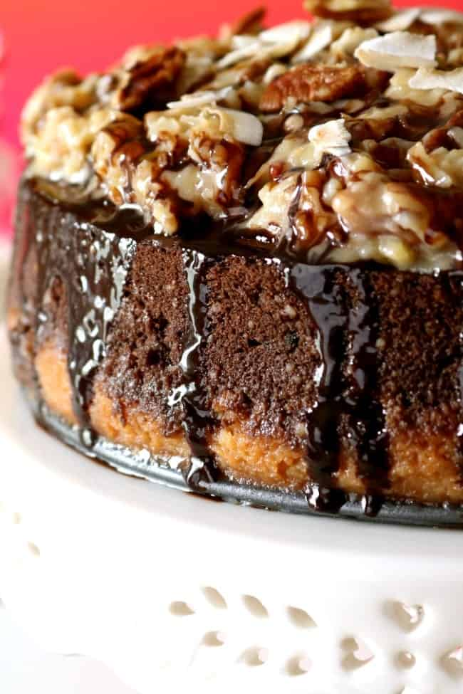 Close-up of the side and coconut-pecan topping of a german chocolate cheesecake.
