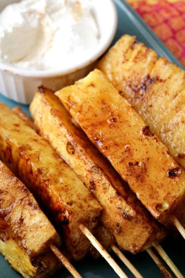 Grilled pineapple spears coated in cinnamon and sugar on a plate with fresh whipped cream.