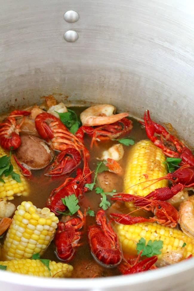 A lowcountry seafood boil overhead view of a pot of shrimp and crawfish boil.