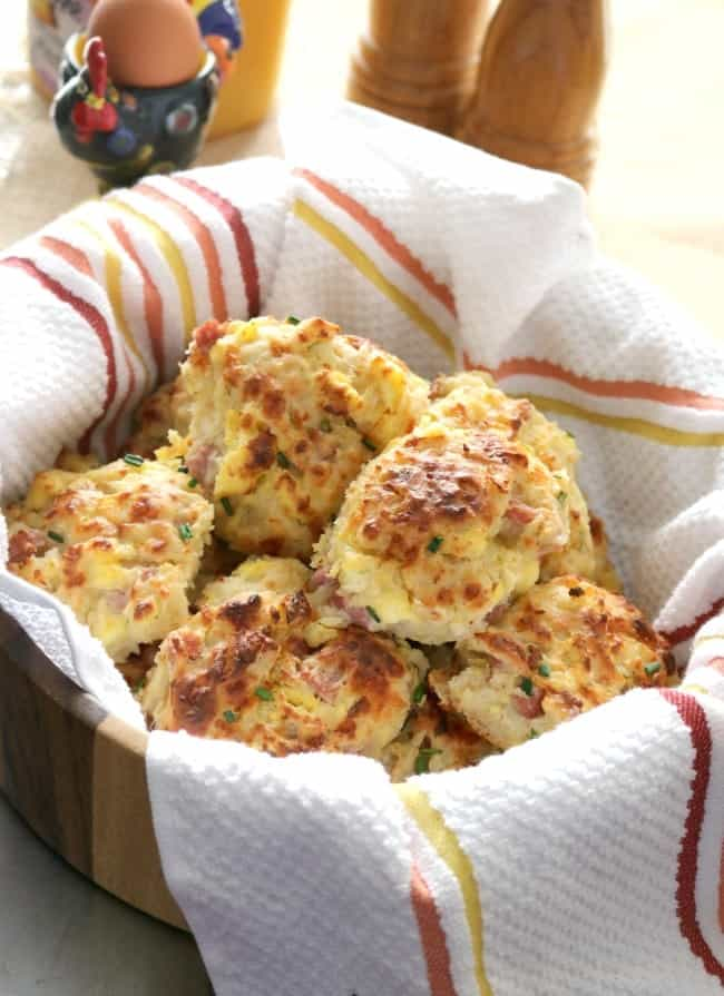 Loaded ham and cheese breakfast biscuits sit in a basket lined with a striped towel.