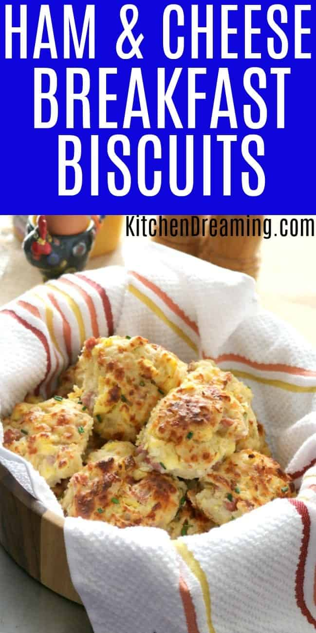 a bowl of freshly baked ham and cheese breakfast biscuits lines with a striped tea towel.