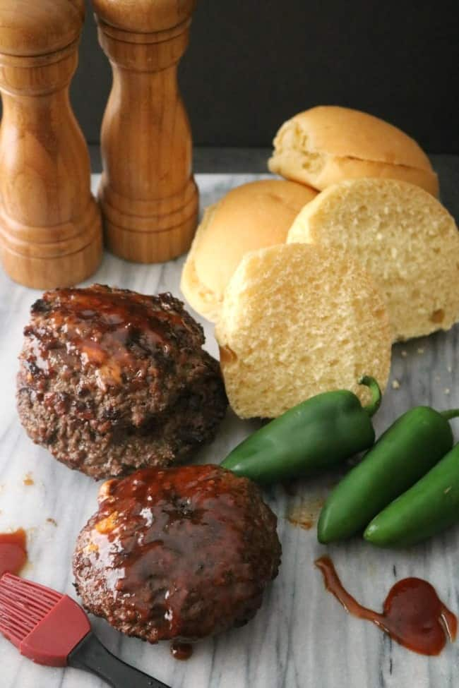 An image of jalapeno-cheese stuffed cheeseburgers glazed with BBQ sauce