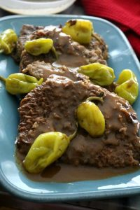 Scratch-made Mississippi Swiss Steaks are tender and juicy covered in a rich, tangy beef gravy. This modified version of the iconic pot roast doesn't use prepackaged seasoning mixes and is still a quick and easy weeknight meal.