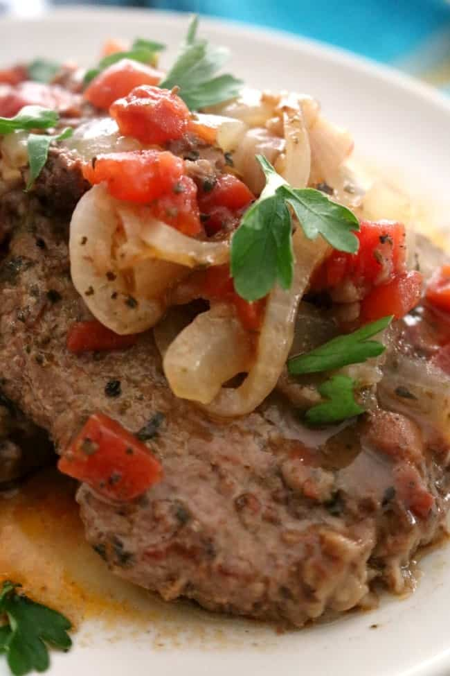 Swiss Steak is a great family-friendly dinner; not only is it easy to make but it's also very affordable. This versatile dish can be prepared either in the oven or in a slow cooker. Easy Swiss Steak combines delicious tender beef with a rich tomato-based gravy and is absolutely perfect served over mashed potatoes, steamed rice, or buttered noodles.