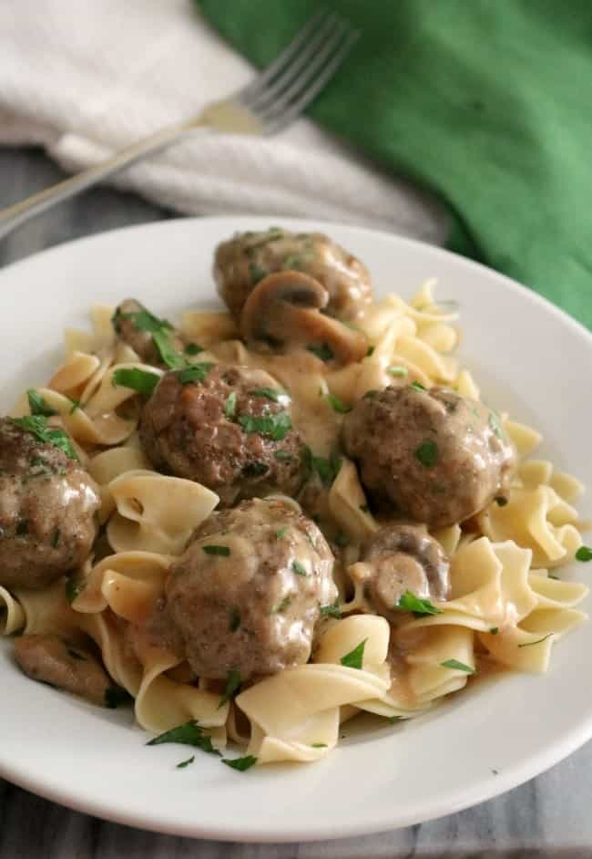 A plate of meatballs stroganoff nestled on top of egg noodles in a luscious sour cream gravy.