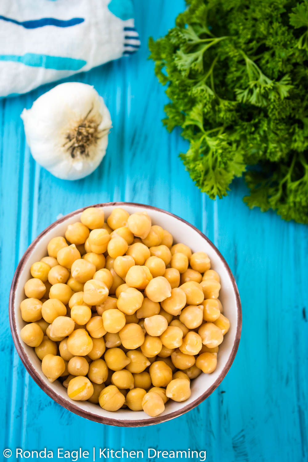 An image of a small, white, ceramic bowl of chick peas on a blue background. Curly Parsley and a head of garlic rest in the background with a blue and white utensil patterned kitchen towel.