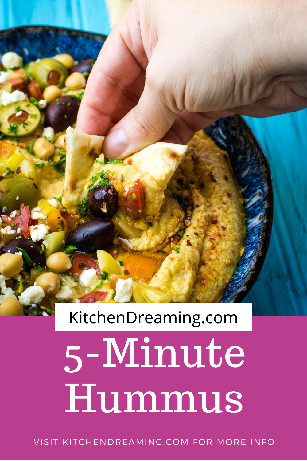 A pinnable image of a bowl of 5-minute hummus. The top of the bowl has been garnished with chopped grape yellow and red grape tomatoes, Kalamata olives, green olives, additional chick peas and a sprinkling of crumbled feta and minced parsley. It was then drizzled with olive out and a dusting of paprika and red pepper flakes. A hand can be seen holding a toasted triangle of pita bread taking a scoop of hummus.