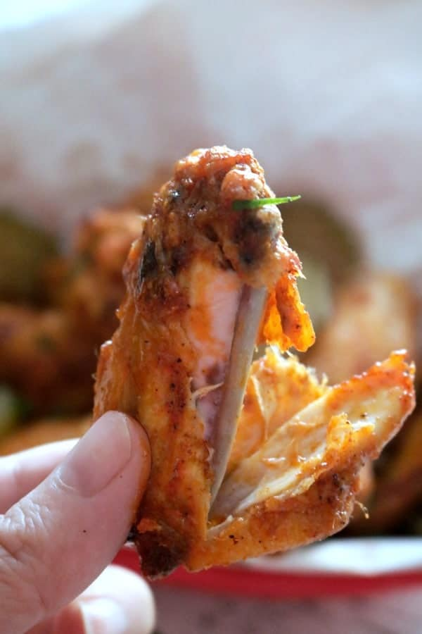 A close up shot of piece of a tender & juicy chicken wing section.