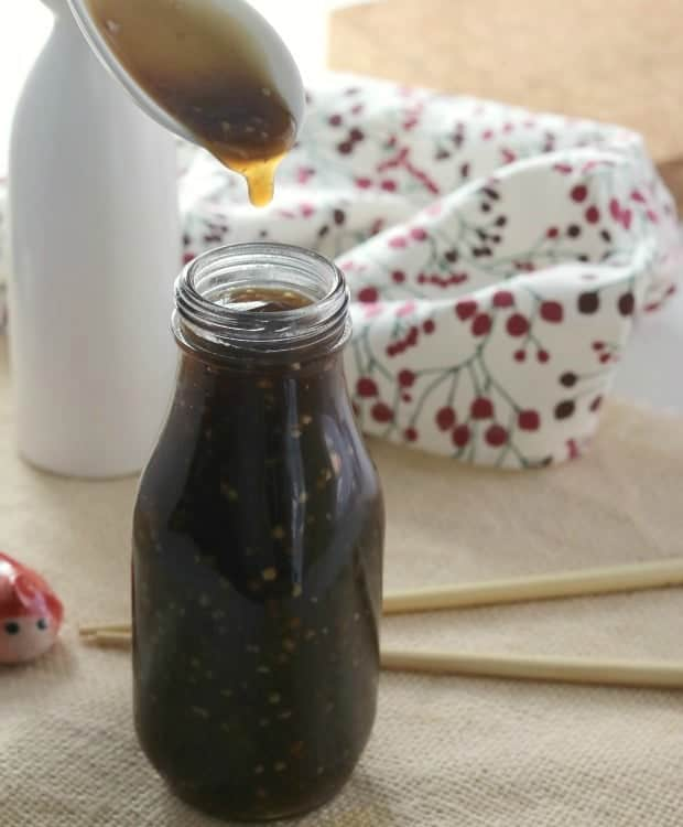 A bottle of Homemade Teriyaki sauce with a dripping spoon.