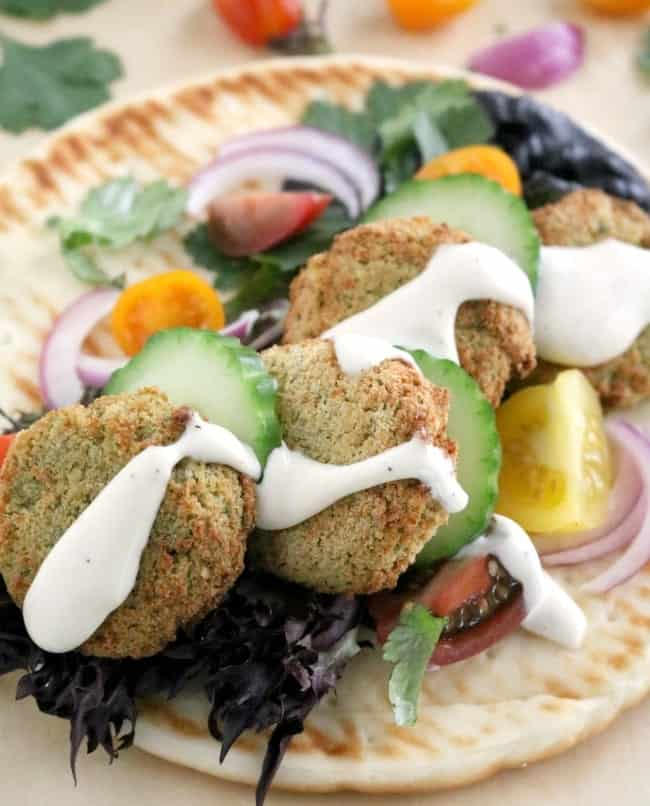 Falafel is a Middle Eastern street food consisting of a small fritter made from ground chickpeas (garbanzo beans), minced garlic, and fresh parsley. Falafel can be eaten plain, with hummus and vegetables, or most frequently tucked into a pita and topped with condiments like hot sauce or a yogurt sauce similar to tzatziki.